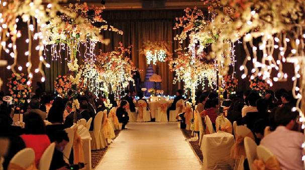 Wedding celebrations at a party hall, guests enjoying the lavish arrangements and decorations.