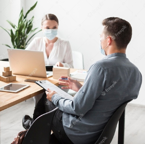 An image of 2 employee working with a mask on their face